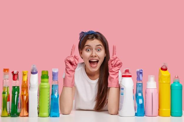 Une jeune femme de ménage optimiste pointe vers le haut avec les deux index, porte un bandeau et des gants en caoutchouc, montre quelque chose de génial au plafond