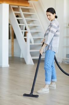 Jeune femme de ménage passer l'aspirateur sur le sol à grande maison