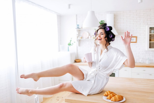 Jeune femme de ménage positive assis sur une table et se présentant à la caméra. rire à haute voix. agitez avec la main. croissants sur plaque. insouciante jeune femme. des bigoudis dans les cheveux. robe de chambre blanche.