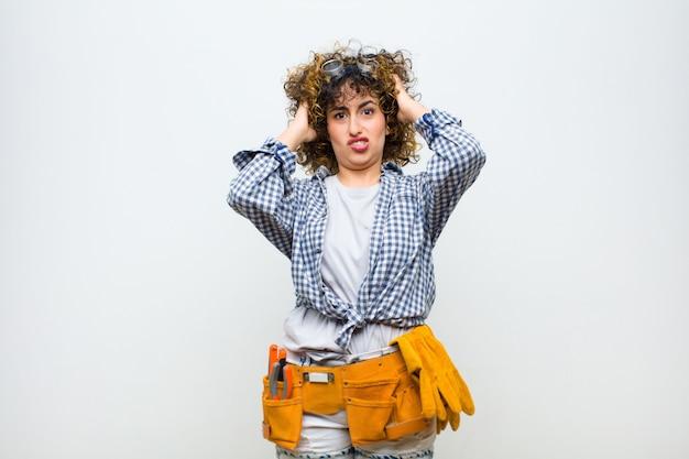 Jeune femme de ménage se sentant frustrée et ennuyée, malade et fatiguée de l'échec, marre des tâches ennuyeuses et ennuyeuses sur le mur blanc