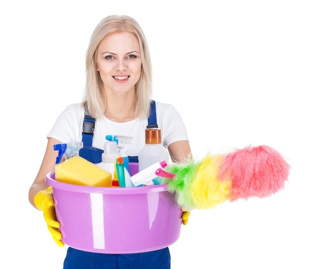 Jeune femme de ménage souriante sur blanc.