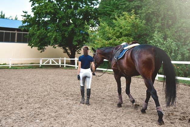 Jeune femme mène son cheval à l'entraînement et le prépare pour les courses d'hippodrome