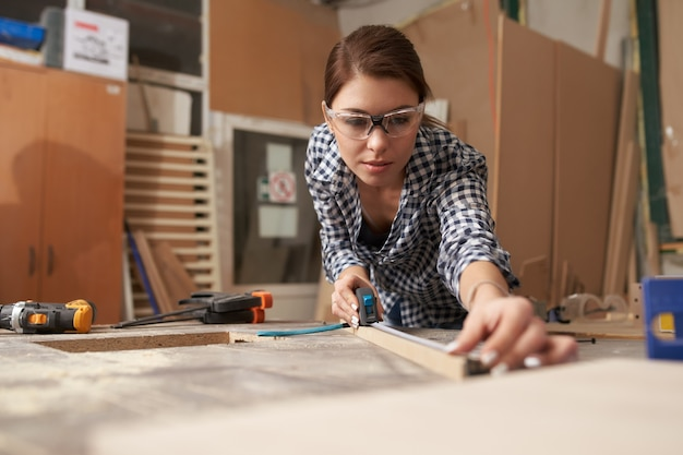 Jeune femme menuisier avec planche de bois derrière l'établi en atelier
