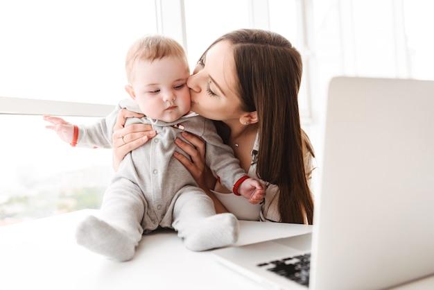 Jeune femme mère utilisant un ordinateur portable avec son petit enfant