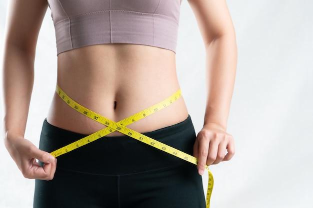 Jeune femme mesurant sa taille de ventre avec du ruban de mesure, concept de mode de vie de régime de femme