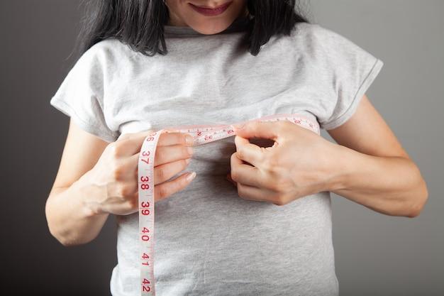 Jeune femme mesurant ses seins avec un ruban
