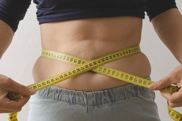 Une jeune femme mesure sa taille avec un ruban à mesurer