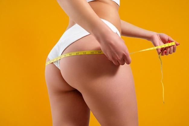 Une jeune femme mesure le volume de ses cuisses avec un ruban centimétrique. sur un fond de couleur jaune.