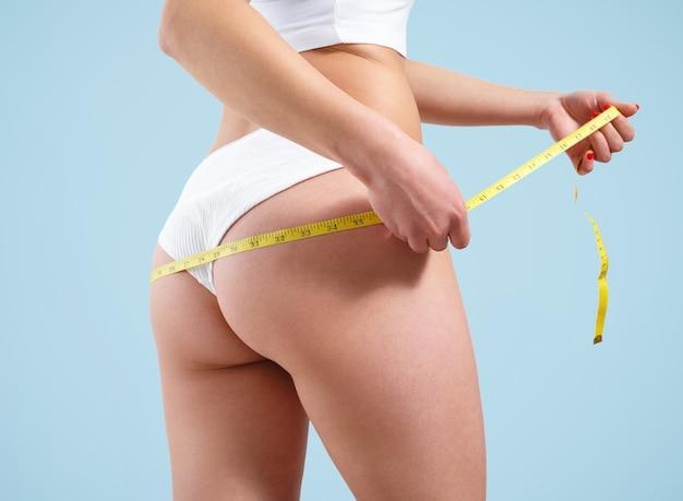 Une jeune femme mesure le volume de son bassin avec un mètre ruban. sur fond bleu.