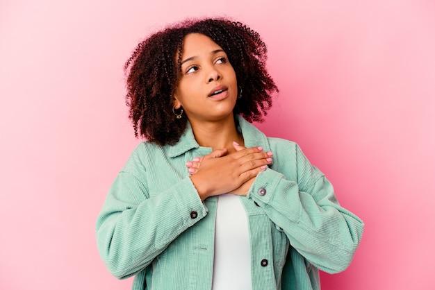Jeune femme métisse afro-américaine isolée a une expression amicale, appuyant sur la paume de la main contre la poitrine. concept d'amour.