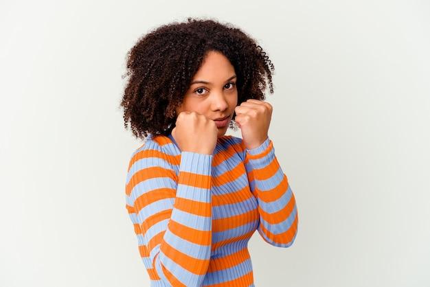 Jeune femme métisse afro-américaine isolée jetant un coup de poing, la colère, les combats en raison d'une dispute, la boxe.