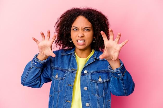 Jeune femme métisse afro-américaine isolée montrant des griffes imitant un chat, geste agressif.