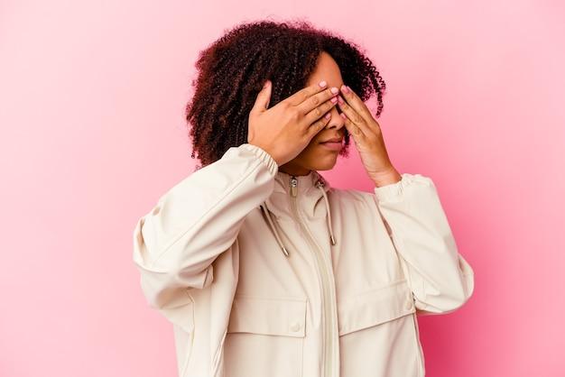 Jeune femme métisse afro-américaine isolée peur couvrant les yeux avec les mains.