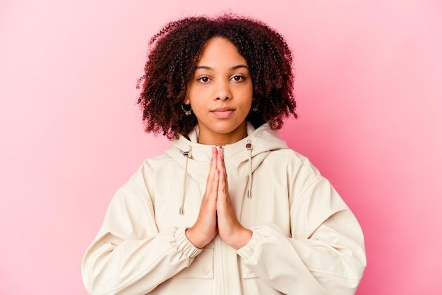 Jeune femme métisse afro-américaine isolée priant, montrant la dévotion, personne religieuse à la recherche d'inspiration divine.