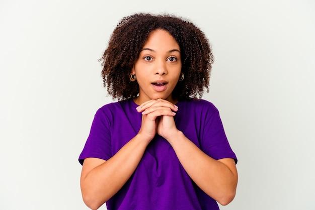 Jeune femme métisse afro-américaine isolée priant pour la chance, étonné et ouvrant la bouche à l'avant.
