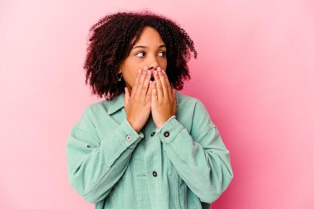 Jeune femme métisse afro-américaine isolée réfléchie à la recherche d'un espace de copie couvrant la bouche avec la main.