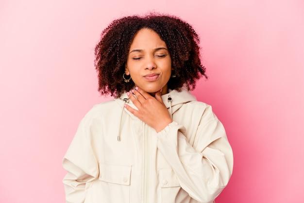Jeune femme métisse afro-américaine isolée souffre de douleurs dans la gorge en raison d'un virus ou d'une infection.