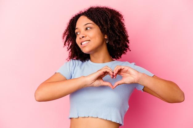 Jeune femme métisse afro-américaine isolée souriant et montrant une forme de coeur avec les mains.