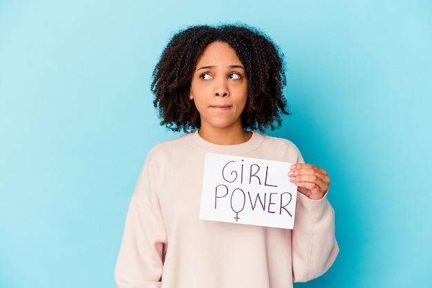 Jeune femme métisse afro-américaine tenant un concept de puissance de fille confuse, se sent douteuse et incertaine.