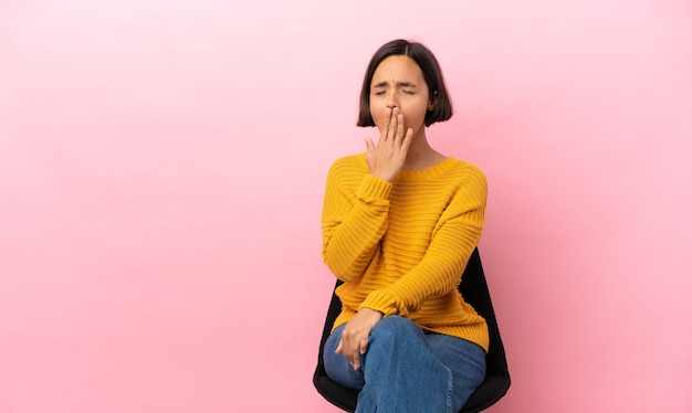 Jeune femme métisse assise sur une chaise isolée sur fond rose bâillant et couvrant la bouche grande ouverte avec la main