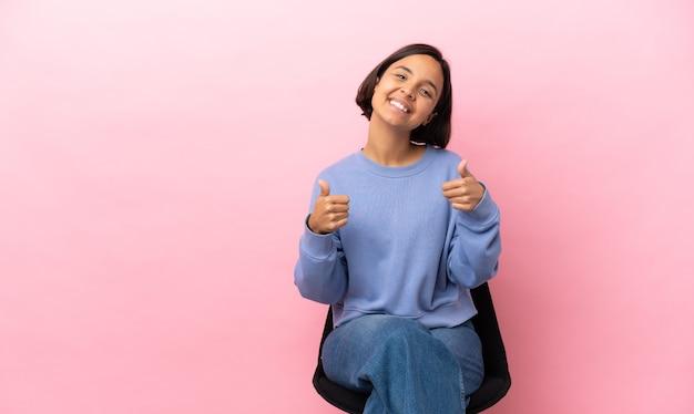 Jeune femme métisse assise sur une chaise isolée sur fond rose donnant un geste du pouce levé