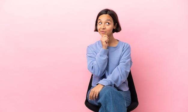 Jeune femme métisse assise sur une chaise isolée sur fond rose pensant à une idée tout en levant les yeux