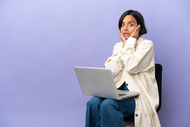Jeune femme métisse assise sur une chaise avec un ordinateur portable isolé sur fond violet frustré et couvrant les oreilles