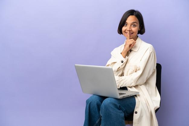 Jeune femme métisse assise sur une chaise avec ordinateur portable isolé sur fond violet montrant un signe de silence geste mettant le doigt dans la bouche