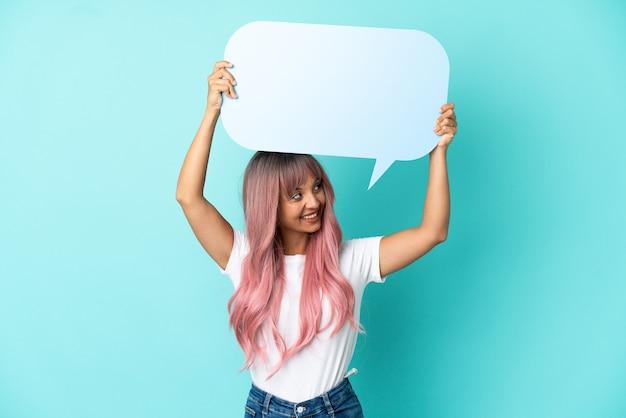 Jeune femme métisse aux cheveux roses isolée sur fond bleu tenant une bulle de dialogue vide