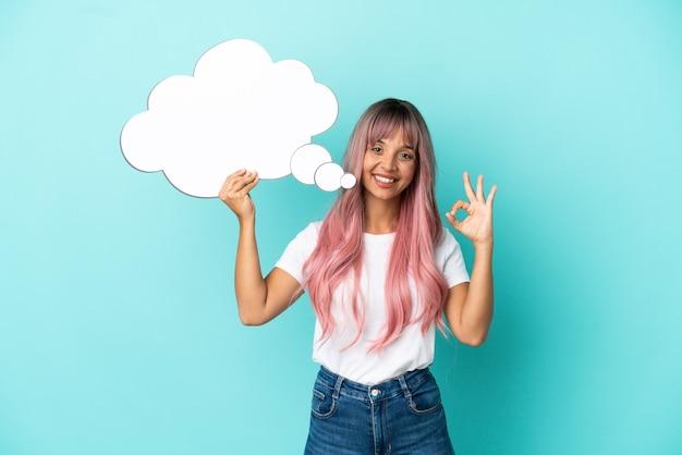 Jeune femme métisse aux cheveux roses isolée sur fond bleu tenant une bulle de pensée et faisant signe ok