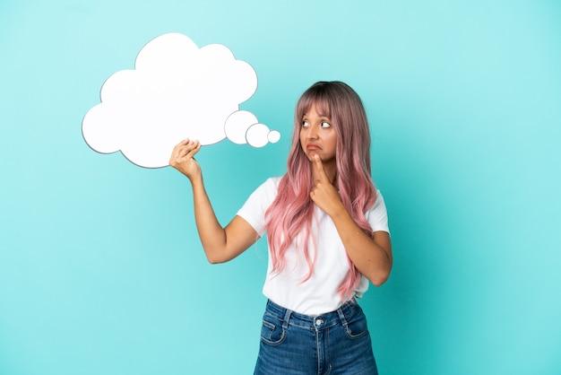 Jeune femme métisse aux cheveux roses isolée sur fond bleu tenant une bulle de pensée