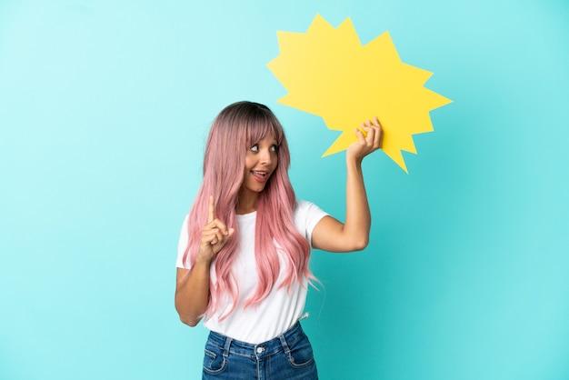 Jeune femme métisse aux cheveux roses isolée sur fond bleu tenant une bulle vide et pensant