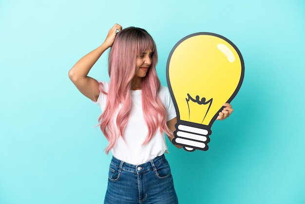 Jeune femme métisse aux cheveux roses isolée sur fond bleu tenant une icône d'ampoule et ayant des doutes