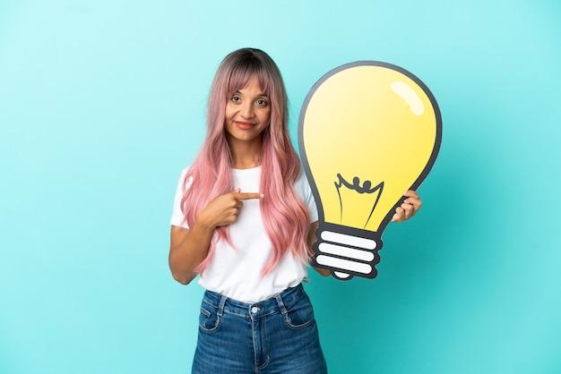 Jeune femme métisse aux cheveux roses isolée sur fond bleu tenant une icône d'ampoule et la pointant