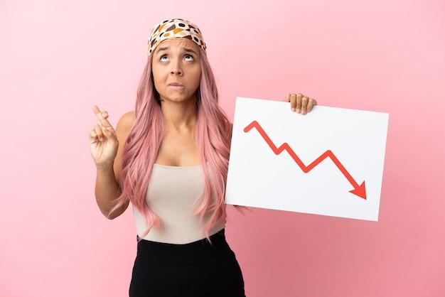 Jeune femme métisse aux cheveux roses isolée sur fond rose tenant une pancarte avec un symbole de flèche de statistiques décroissantes avec les doigts qui se croisent