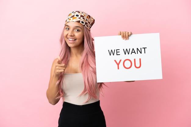 Jeune femme métisse aux cheveux roses isolée sur fond rose tenant le panneau we want you et pointant vers l'avant