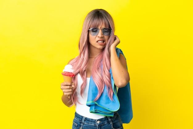 Jeune femme métisse aux cheveux roses tenant une glace isolée sur fond jaune frustré et couvrant les oreilles