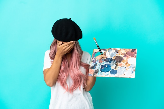 Jeune femme métisse aux cheveux roses tenant une palette isolée sur fond bleu avec une expression fatiguée et malade