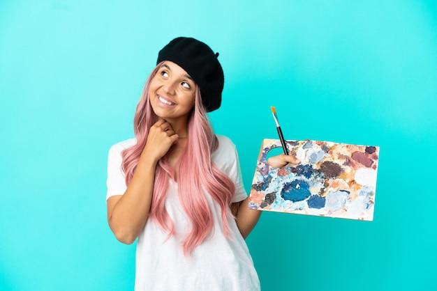 Jeune femme métisse aux cheveux roses tenant une palette isolée sur fond bleu en levant tout en souriant