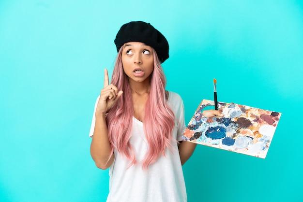Jeune femme métisse aux cheveux roses tenant une palette isolée sur fond bleu pensant à une idée pointant le doigt vers le haut