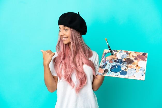 Jeune femme métisse aux cheveux roses tenant une palette isolée sur fond bleu pointant sur le côté pour présenter un produit