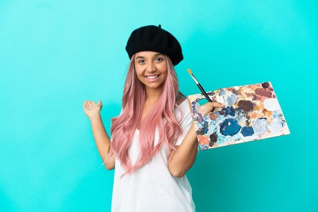 Jeune femme métisse aux cheveux roses tenant une palette isolée sur fond bleu tendant les mains sur le côté pour inviter à venir