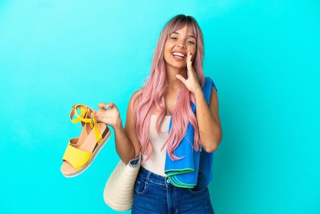 Jeune femme métisse aux cheveux roses tenant des sandales d'été isolées sur fond bleu criant avec la bouche grande ouverte