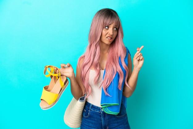 Jeune femme métisse aux cheveux roses tenant des sandales d'été isolées sur fond bleu avec les doigts croisés et souhaitant le meilleur