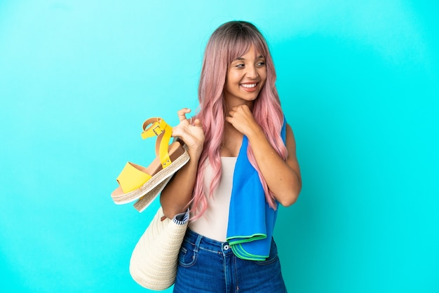 Jeune femme métisse aux cheveux roses tenant des sandales d'été isolées sur fond bleu en levant tout en souriant