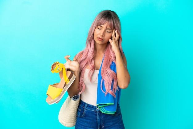 Jeune femme métisse aux cheveux roses tenant des sandales d'été isolées sur fond bleu avec des maux de tête