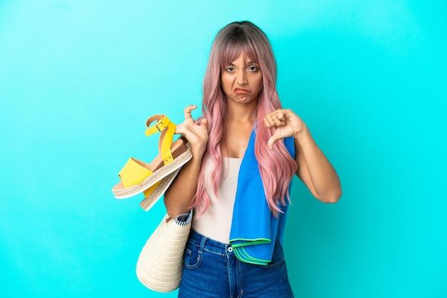 Jeune femme métisse aux cheveux roses tenant des sandales d'été isolées sur fond bleu montrant le pouce vers le bas avec une expression négative
