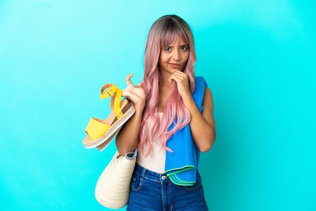 Jeune femme métisse aux cheveux roses tenant des sandales d'été isolées sur fond bleu pensant