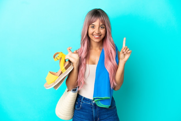 Jeune femme métisse aux cheveux roses tenant des sandales d'été isolées sur fond bleu pointant vers une excellente idée