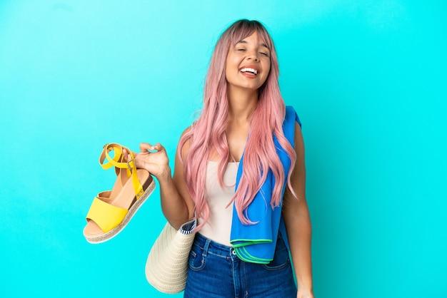 Jeune femme métisse aux cheveux roses tenant des sandales d'été isolées sur fond bleu en riant